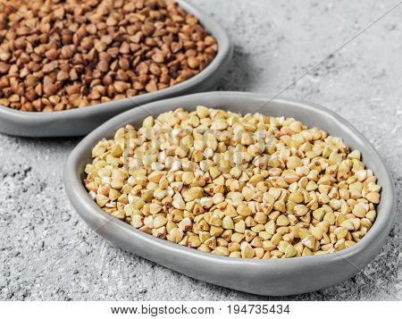 Close up view of raw green buckwheat in trendy plate and brown roasted buckwheat on background. Healthy food and diet concept
