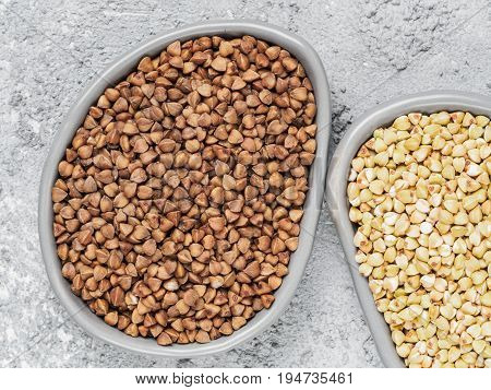 Top view of brown roasted buckwheat and raw green buckwheat in trendy plates on gray concrete background. Healthy food and diet concept. Flat lay. Copy space.