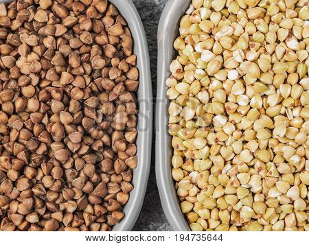 Top view of raw green buckwheat and brown roasted buckwheat on gray concrete background. Healthy food and diet concept. Flat lay. Copy space.