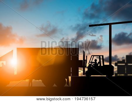 Silhouette Forklift truck lifting cargo container on a truck in the warehouse over blurred natural background sunset pastel.Business Logistics and Transportation concept.