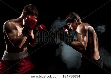 Two professional boxer boxing on black smoky studio background.