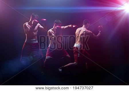 The male athlete boxer punching with dramatic edgy lighting in a dark studio. Image made with stroboscope