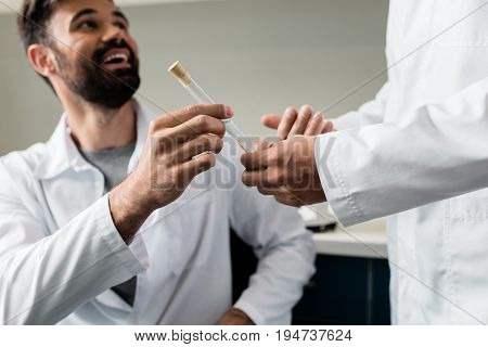 Cropped Shot Of Chemists In Lab Coats Holding Test Tube With Reagent Together