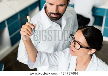 Professional Young Chemists In White Coats Examining Test Tube With Reagent In Chemical Lab