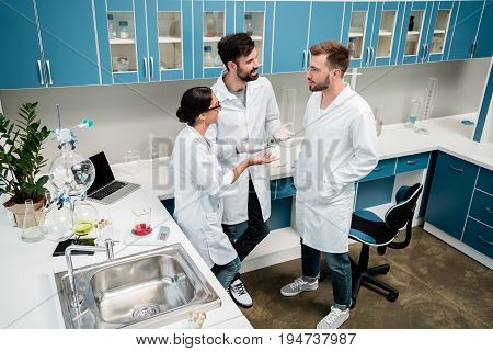 Smiling Young Colleagues In White Coats Standing And Talking In Chemical Lab