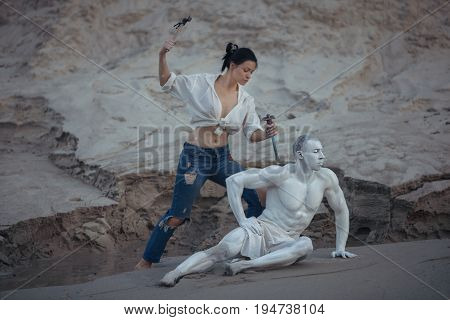 Woman carves a sculpture of a man from a stone.