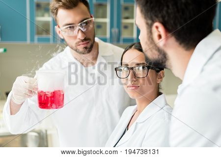 Team Of Professional Young Chemists Wearing Eyeglasses And Lab Coats Making Experiment