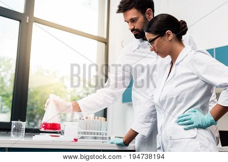 Focused young chemists in white coats making experiment while working in laboratory