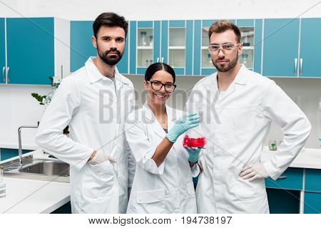Professional Young Scientists In White Coats Holding Flask With Reagent And Smiling At Camera In Che