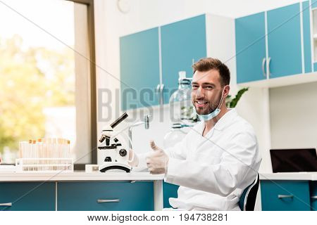 Smiling Bearded Scientist In Lab Coat Showing Thumb Up While Working With Microscope In Lab