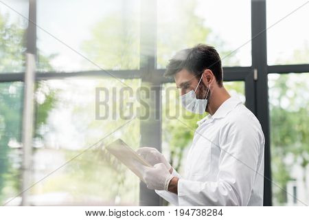 Male Scientist In Protective Workwear Using Digital Tablet In Laboratory