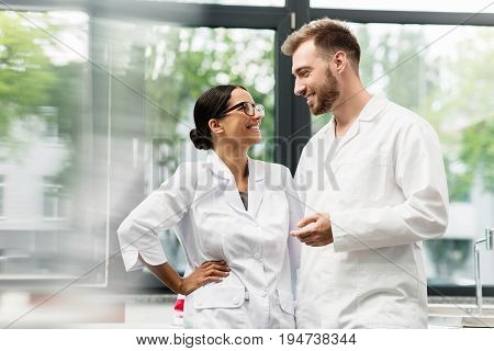 Cheerful Young Scientists In White Coats Smiling Each Other In Lab