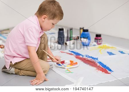 Cute kid boy sitting on the floor and drawing with colorful paints. Child making flag craft. Education creativity school activities.
