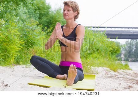 Hatha yoga. Seated half lotus, Yoga poses, asan. Concept of healthy life and natural. Practicing yoga, sitting and fold one's hands in namaste, wearing sportswear, bra. Nature, park, outdoor