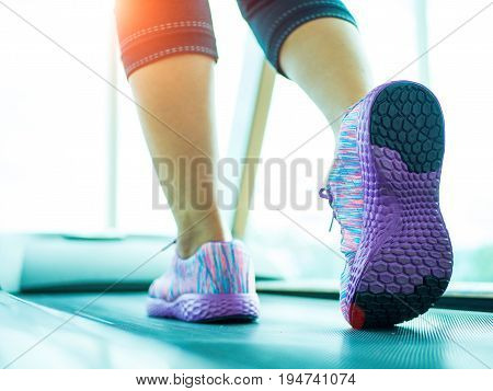 Woman step and running on the treadmill in the gym fitness