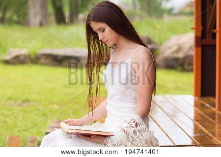Pretty Woman In White Dress Reading Book In The Cloudy Nature. Girl Sits On The Terrace Or On The Po