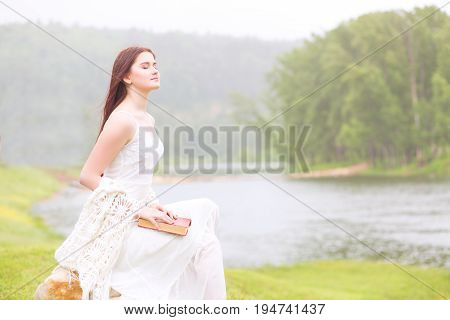 Girl In A Rainy Park Reading A Book