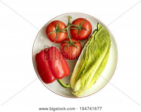 Whole fruits of fresh vegetables: Bulgarian pepper tomato branch and romaine salad lie on white round porcelain plate with pomegranate rim close-up on white background