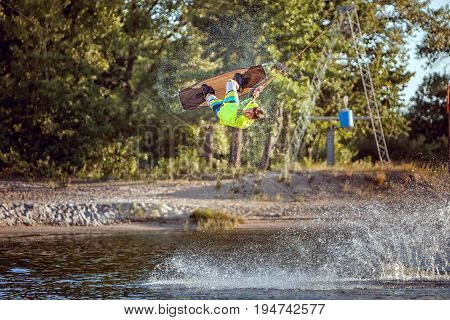 Sportsman wakeboarder during the jump. He jumped high above the lake. Extreme sport for men.