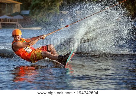 Man glides on the board on the lake. He quickly rushes creating splashes and splashes of water.