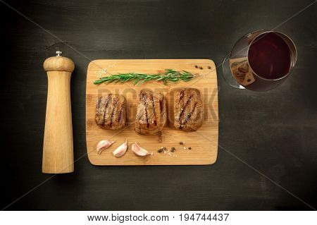 Three slices of cooked meat, beef fillet, shot from above on a black texture with a sprig of rosemary, garlic cloves, salt, and pepper, with a glass of red wine, a pepper grinder, and a place for text