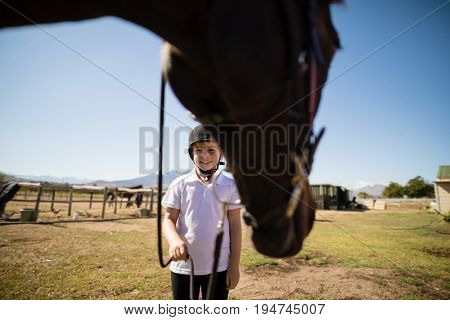 Smiling girl holding the rein of the horse in the ranch on a sunny day