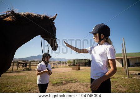 Two girls standing with a horse in the ranch on a sunny day