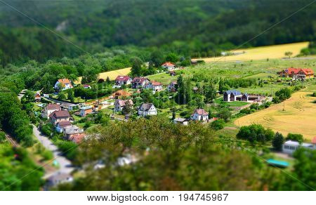 Beautiful village with houses in valley shot with tilt shift effect.