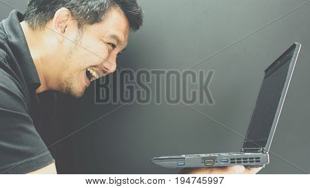 Asian Man Hold Computer Notebook In Laugh Gesture