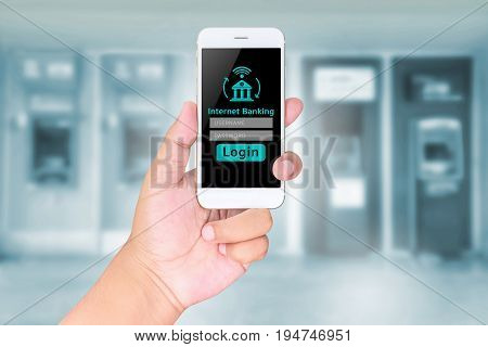Man Hand Hold Mobile Banking On A Smart Phone On Blurred Abstract Background Of Atms Machine