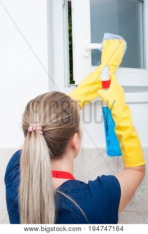 Housekeeper Cleaning Window With Rag And Detergent Spray