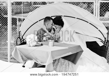 Beautiful Wedding Couple Enjoying Each Other's Comany On A Bench On A Lakeside. Black And White Phot