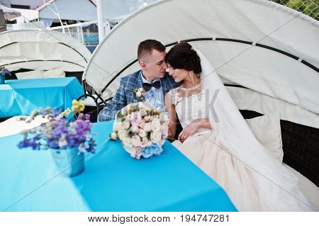 Beautiful Wedding Couple Enjoying Each Other's Comany On A Bench On A Lakeside.