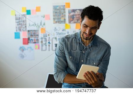 Young man using tablet against adhesive notes at creative office