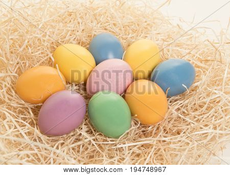 Colored easter eggs lying in a nest on a white background
