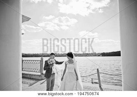 Stunning Wedding Couple Walking On Lakeside On A Sunny Day. Black And White Photo.