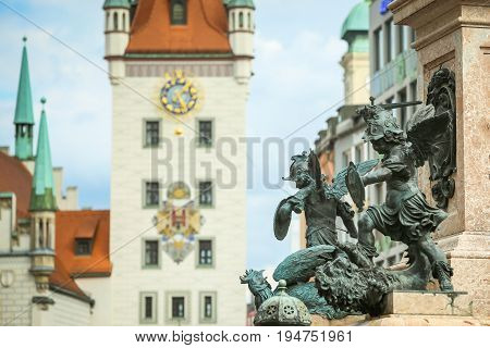 MUNICH GERMANY - MAY 9 2017 : The pedestal of Virgin Mary Statue with putto statue and the Old Town Hall at Marienplatz in Munich Germany.