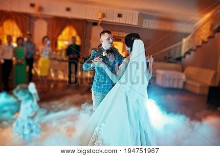 Beautiful Wedding Couple Dancing Their First Dance In A Restaurant With People In The Background.