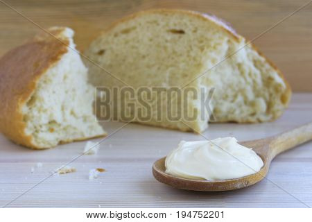 Sour cream in wooden spoon and white bread on wooden background.