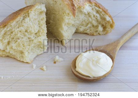 Sour cream in wooden spoon and white bread on light wooden background.