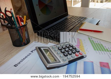 Business desktop with laptop calculator and financial reports top view. Financial accounting concept. Calculator on business earning report with financial chart and graph on screen laptop on desk