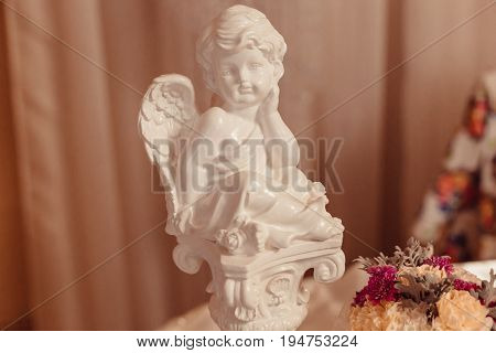 Little Porcelain Angel Stands Behind The Bouquet