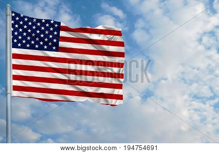 National flag of America on a flagpole in front of blue sky.