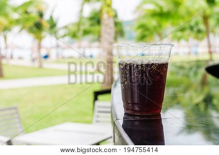 Cola or Cuba Libre cocktail drink in glass at the bar on the beach