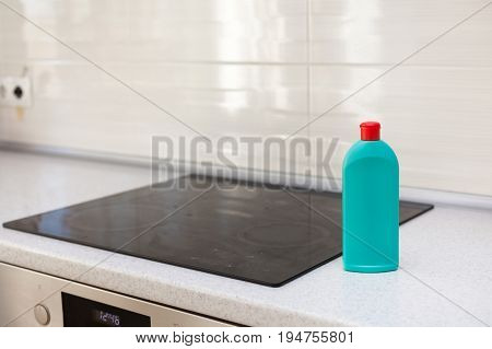House cleaning - plastic bottles with detergents on kitchen tabletop. Washing of the hob. Induction stove. Electric stove