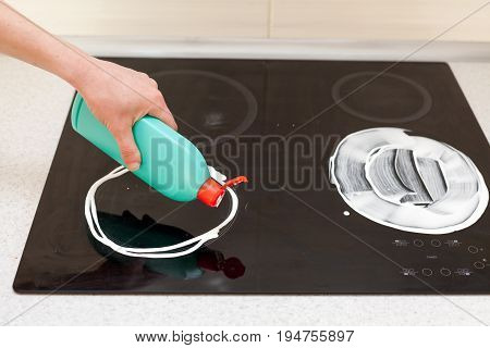 Woman hands with bottle of cleaning detergent for induction stove applies a liquid scour to the burner.