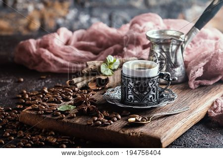Turkish coffee in traditional embossed metal cup with coffee beans on black backfround. Toned photo
