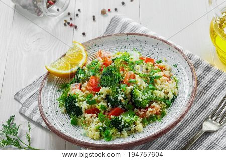Plate with couscous and vegetables on a rustic white wooden table. Traditional eastern healthy meal made of couscous broccoli tomato pepper onion and dill. Top view.