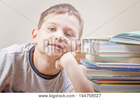 Little kid near stack of colorful books