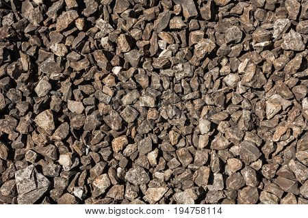 Small gray and brown stones on a ground. Natural material background